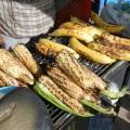 Kochbananen und gegrillte Maiskolben werden an kleinen Ständen am Straßenrand verkauft